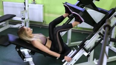 Attractive young blonde woman doing strength training on a gym. Pumping leg muscles.