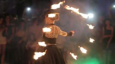 Amazing fireshow by young woman and man on a street.