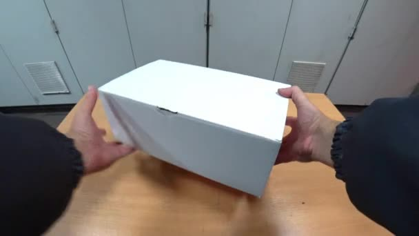 The worker takes out of the box and looks at the protective shoes. Preparation for work, personal protective equipment. POV action camera shot.