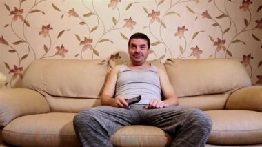 Adult caucasian man watching TV and emotional changing channels with remote control. Sitting on a sofa at home.