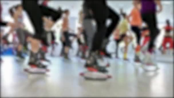 Group of young sporty caucasian women doing fitnes exercises with kangoo jumps shoes in a gym.