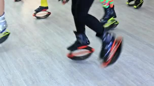 KIEV, UKRAINE - MARCH 2018. Group of young sporty caucasian women doing fitnes exercises with kangoo jumps shoes in a gym.