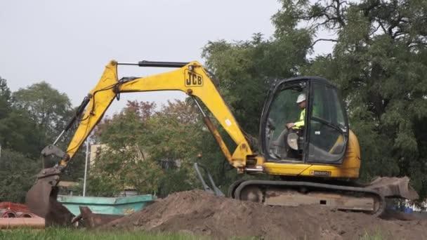Vratislav, Polsko - říjen. 2019: Žlutý bagr pracuje na ulici města. Těžká průmyslová zařízení.