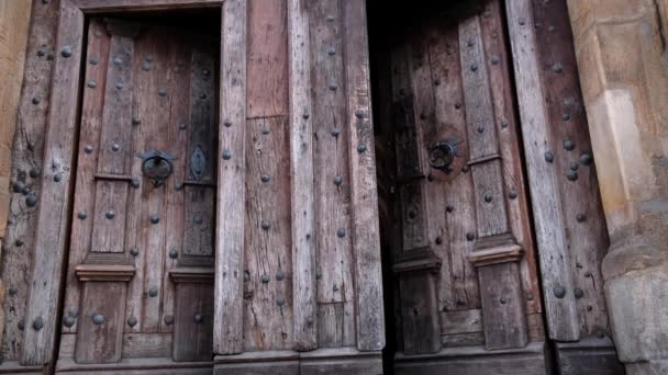 Close-up of closing two old wooden doors with metal handles in ancient medieval Catholic church. For religion, histotic, architecture background.