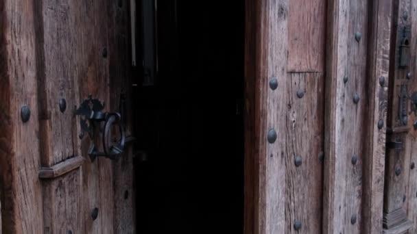 Nahaufnahme des Schließens einer alten Holztür mit Metallgriff in einer mittelalterlichen katholischen Kirche. Für Religion, Historie, Architektur.
