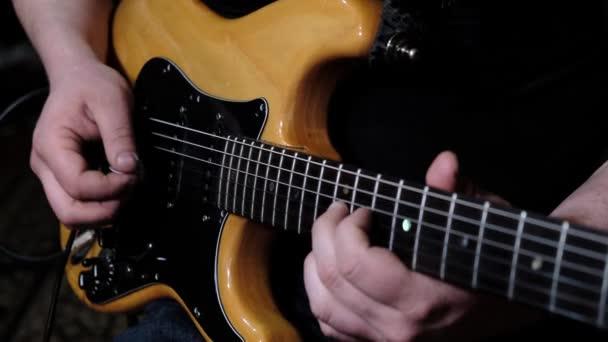 Muž hlavní kytarista hraje na elektrickou kytaru na koncertě v klubu.