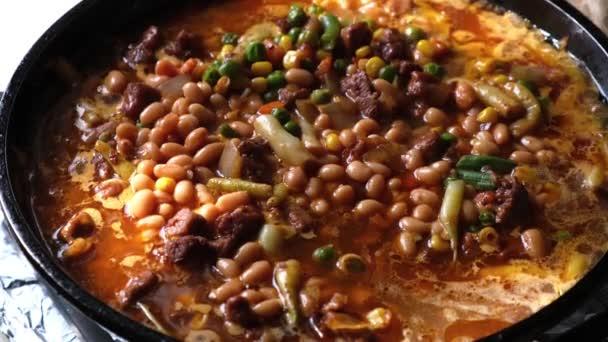 Kousky šťavnatého čerstvého vepřového masa se zeleninou dušené v omáčce na pánvi s párou zblízka.