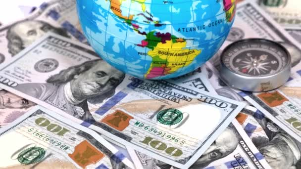 Close-up of Compass and Globe of Planet Earth on a Background of Many 100 Dollars Banknotes on Rotating Table. Travel, tourism, adventures Concept.