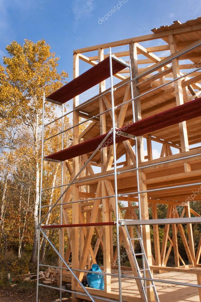металлические строительные леса вокруг недостроенный дом