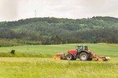 Práce na zemědělské farmě. Červený traktor škrty louka