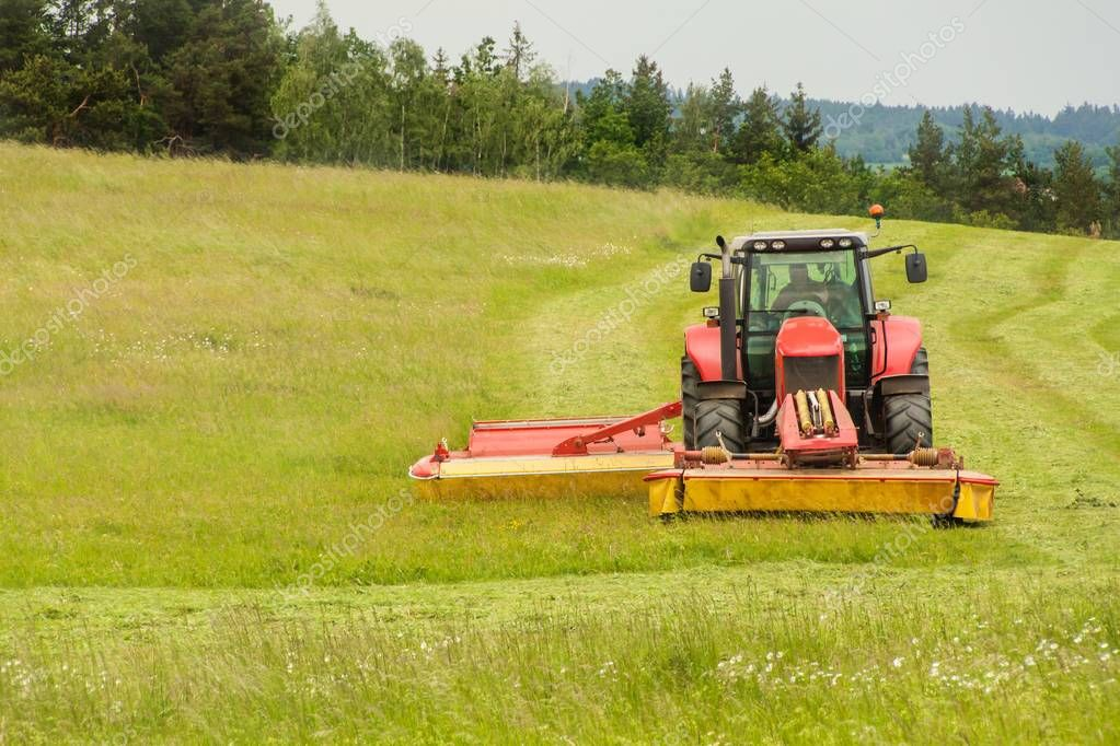 Work on an agricultural farm. A red tractor cuts a meadow.