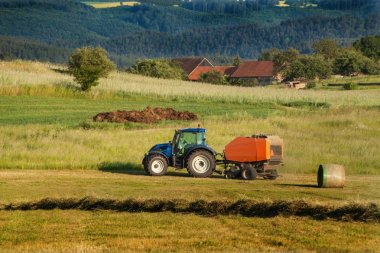 Blue tractor collects dry hay. Agricultural work on the farm in the Czech Republic.