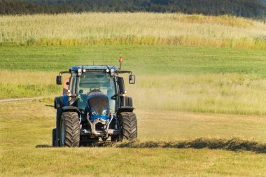Blue tractor on the pasture.. Agricultural work on the farm in the Czech Republic.