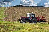 Červený traktor v poli. Zemědělské zemědělské práce. Zemědělství v České republice