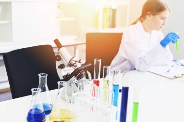 Young female scientist doing some research working conduct experiments and microscope in modern laboratory / Scientists in lab biochemistry genetics forensics microbiology and test tube female doctor
