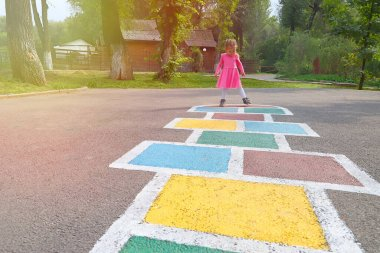 Little girl in a pink dress playing hopscotch on playground outdoors, children outdoor activities