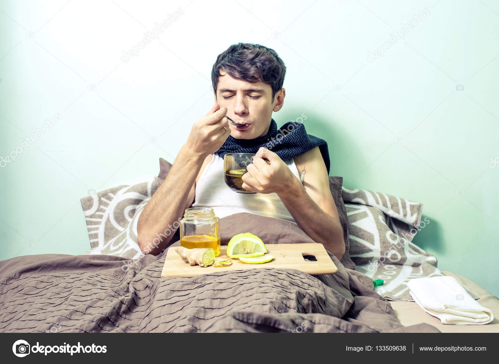 junger mann liegt mit erk ltungen und grippe krank im bett stockfoto artoleshko 133509638. Black Bedroom Furniture Sets. Home Design Ideas