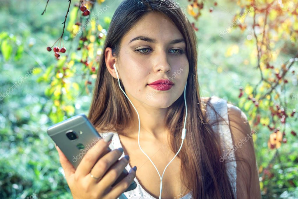 Woman listening to music in your phone wearing headphones on a Sunny day. Concept of audiobooks and student education
