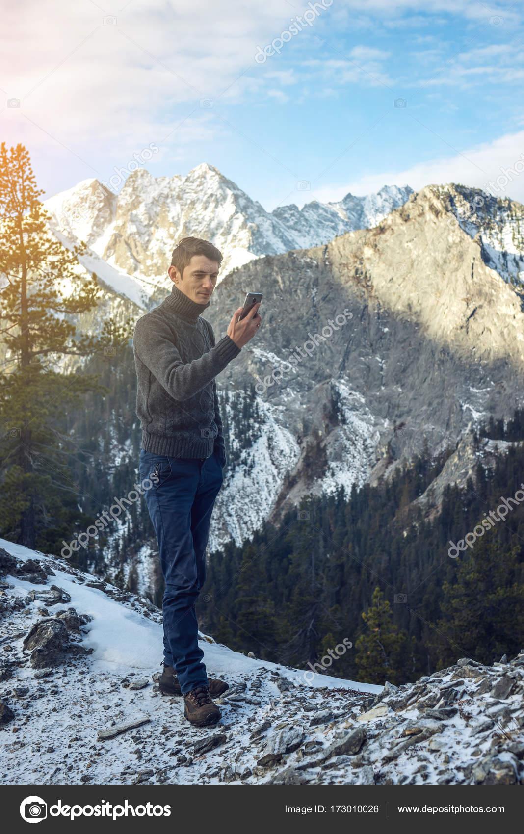 Giovane Uomo In Un Maglione Con Il Telefono In Mano Sulla Montagna