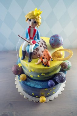 Big kids beautiful cake decorated in the form of the planet with the mastic figurines of the little Prince and the Fox