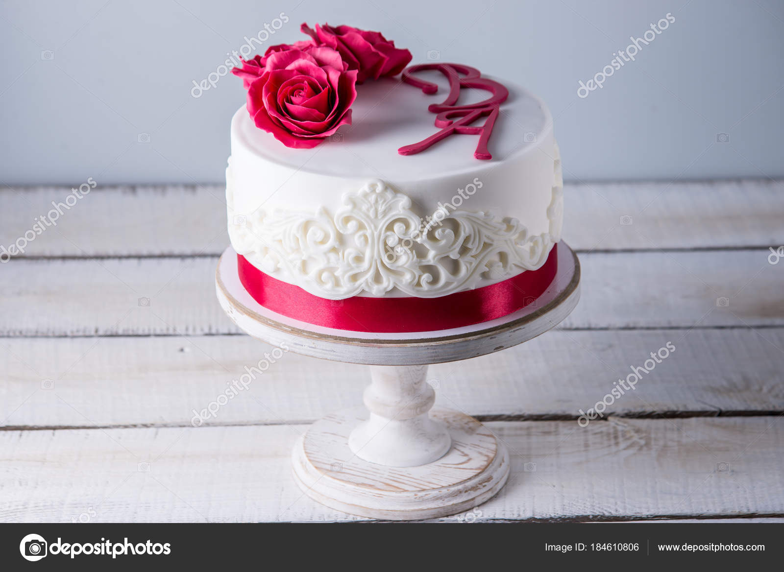 Beautiful white wedding cake decorated with flowers red roses and ...
