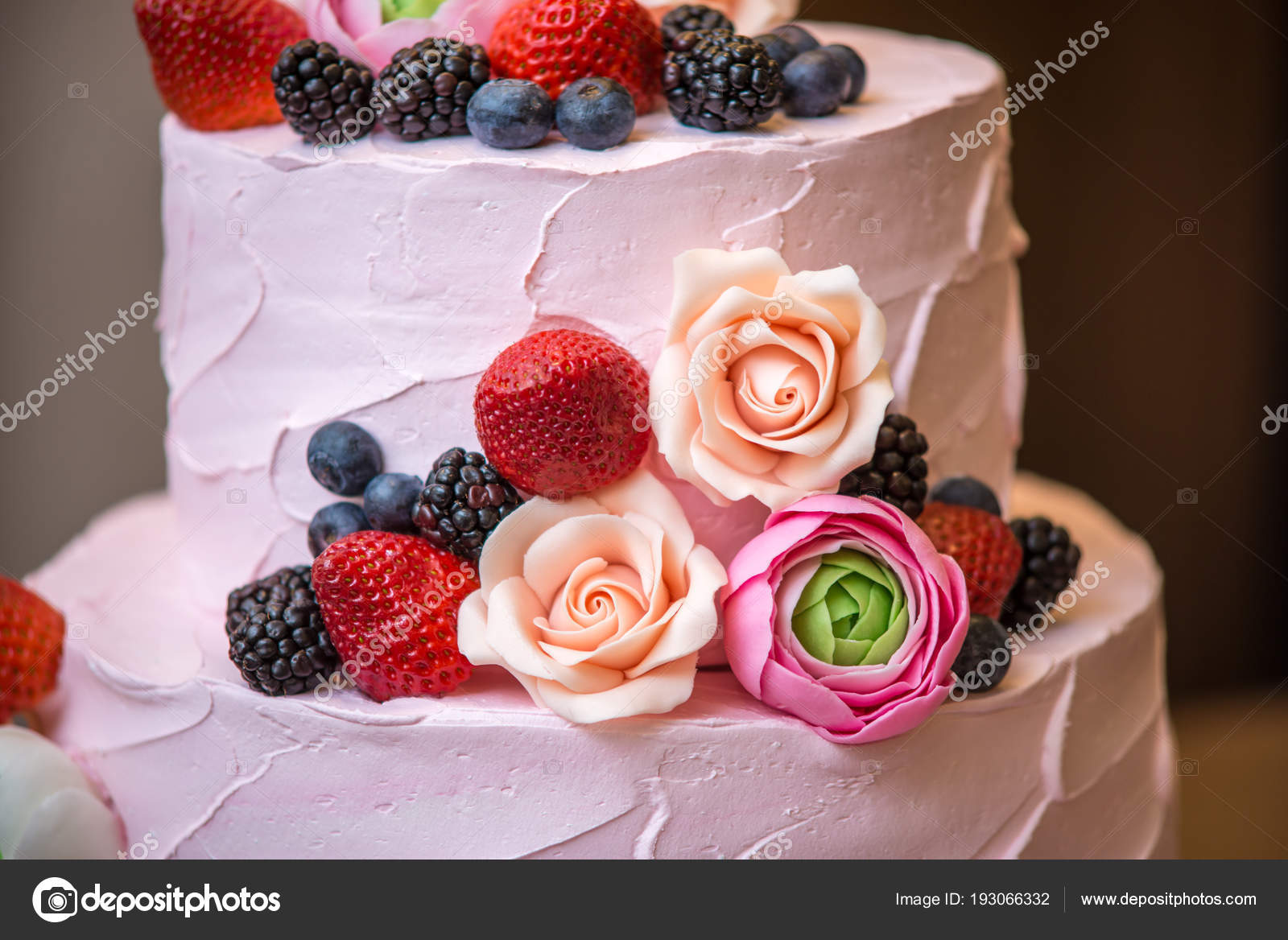 Three tiered pink wedding cake decorated with berries and flowers ...