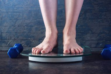 Female feet standing on electronic scales for weight control on dark background. Concept of sports training, diets