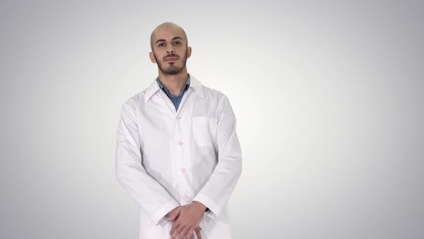 Stehen junge seriöse arabische Arzt auf Gradienten Hintergrund.