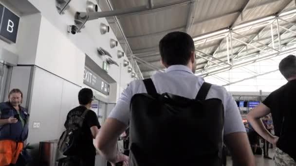 Praha, Česká republika. - 1. srpna 2019: Muž při pohledu na monitory s odlety a přílety na letiště.