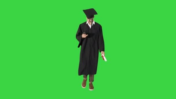 Mladý absolvent student pomocí telefonu při chůzi na zelené obrazovce, Chroma Key.