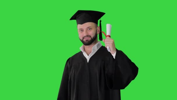 Young male smiling graduate showing thumb up on a Green Screen, Chroma Key.