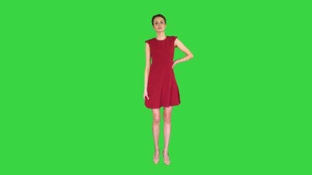 Krásná mladá žena s krátkými vlasy v červených šatech pózuje na zelené obrazovce, Chroma Key.