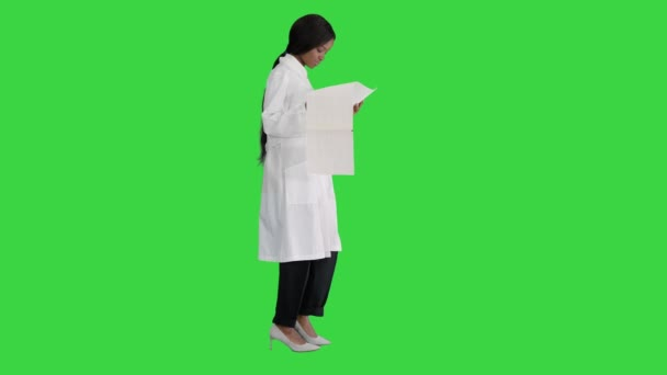 Afro american doctor woman walking and looking at cardiogram record on a Green Screen, Chroma Key.