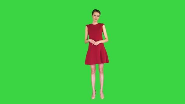Model žena v červených šatech představuje něco ukazující s rukou na nějakém předmětu na zelené obrazovce, Chroma Key.