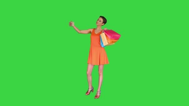 Atraktivní mladá žena drží různé prázdné nákupní tašky dělat selfie na zelené obrazovce, Chroma Key.