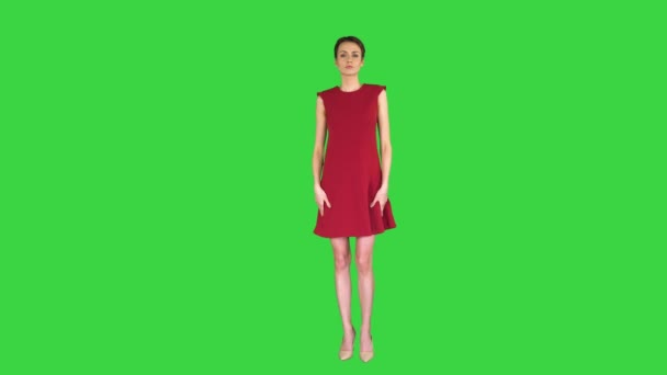 Girl in a red dress, posing, straightens her dress on a Green Screen, Chroma Key.