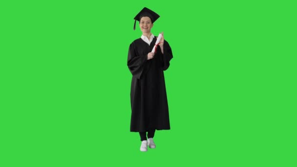 Beautiful young woman graduate is looking at the camera and smiling on a Green Screen, Chroma Key.