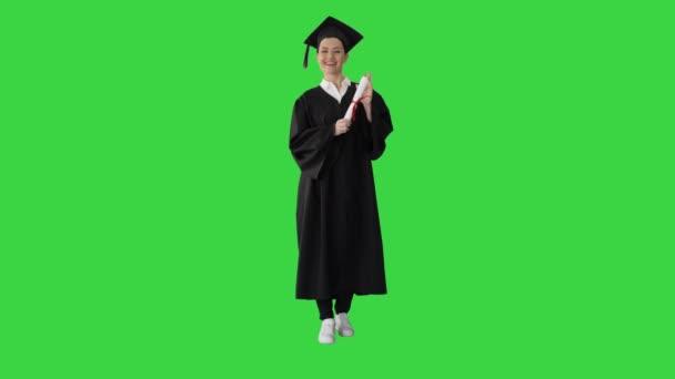 Krásná mladá žena absolvent se dívá do kamery a usmívá se na zelené obrazovce, Chroma Key.