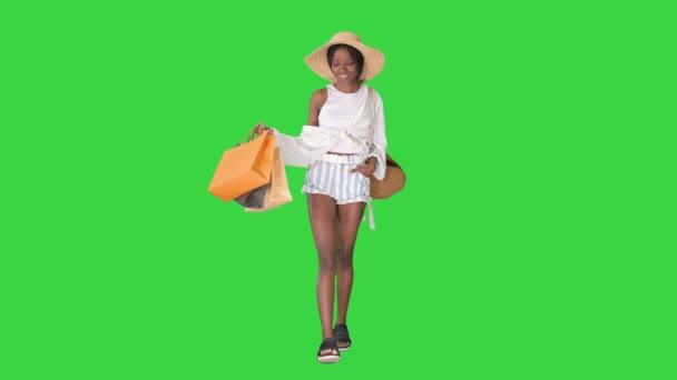 Stilvolle junge Afro-Frau, die mit Einkaufstaschen auf einem Green Screen läuft, Chroma Key.