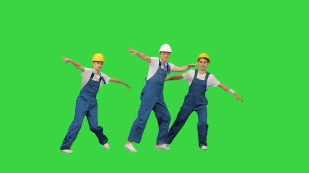 Tři kavkazští stavební dělníci tančící na zelené obrazovce, Chroma Key.