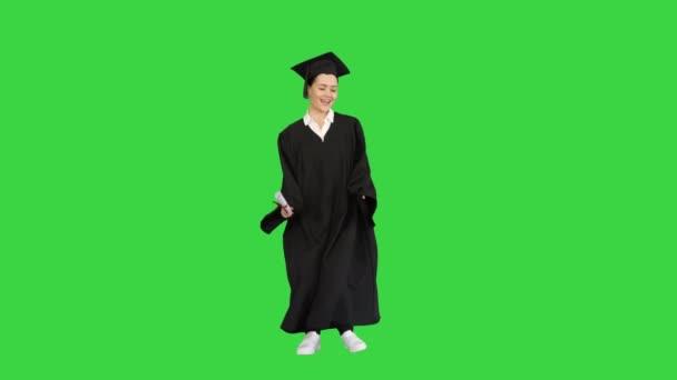 Oktatás, érettségi koncepció Graduate girl dancing on a Green Screen, Chroma Key.