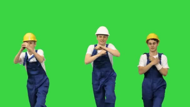 Three dancing construction workers in hard hats on a Green Screen, Chroma Key.