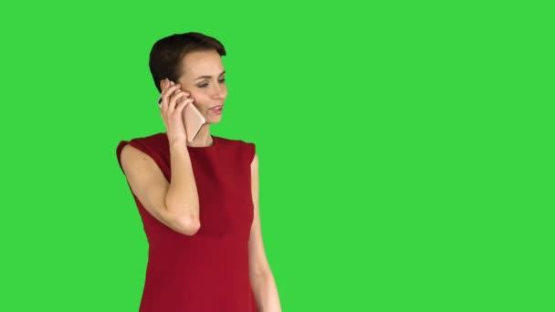Nette hübsche Dame, die auf einem grünen Bildschirm mit dem Handy spricht, Chroma Key.
