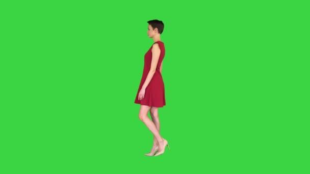 Dívka se snaží červené šaty otočit jako v zrcadle na zelené obrazovce, Chroma Key.
