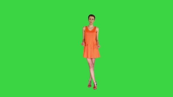 Překvapená nebo šokovaná mladá žena v oranžových šatech na zelené obrazovce, Chroma Key.