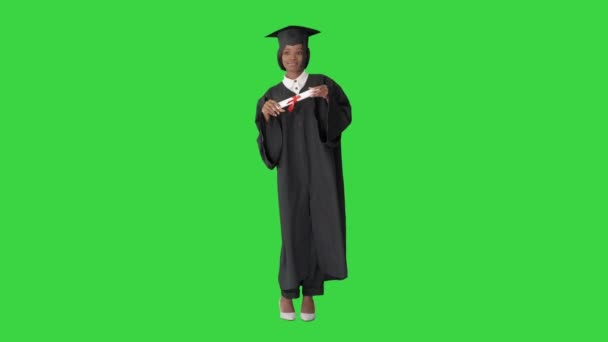 Happy afro graduating female student dancing on a Green Screen, Chroma Key.