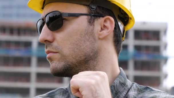 Real construction worker in sunglasses standing at construction site.