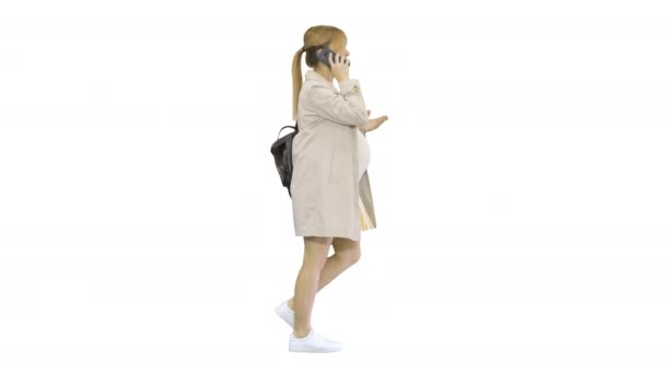 Pregnant woman with backpack walking and talking on the phone on white background.