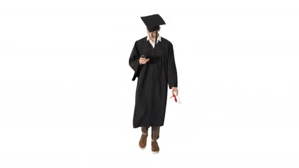 Young graduate student using a phone while walking on white background.
