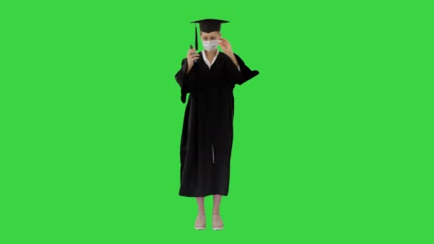 Graduation student in medical mask using sanitizer on a Green Screen, Chroma Key.
